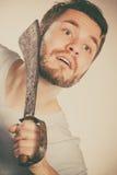 Young man shaving having fun with machete. Royalty Free Stock Photo