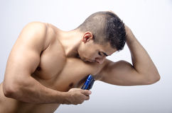 Young man shaving his armpit. Shaving armpit, male beauty, on blue background Stock Photography