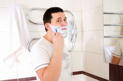 Young man shaving in his bathroom Stock Photo