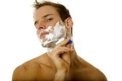 Young man shaving his beard Stock Photo