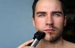 Young man shaving his beard with electric shaver. He shaved half of beard. Young man shaving his beard with electric shaver. He shaved half of beard on grey Stock Photos
