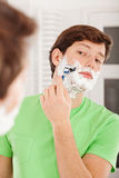 Young man shaving his beard Stock Image