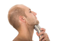 Young man shaving his beard off with an electric razor Royalty Free Stock Photography