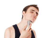 Young man shaving his beard off with an electric razor. Isolated Royalty Free Stock Photo