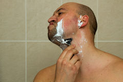 Young man shaving his beard with razor reflected Royalty Free Stock Images