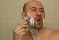 Young man shaving his beard with razor reflected Stock Photos