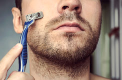 Young man shaving his beard with a razor. Close up on the background of the bathroom Stock Images