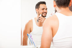 Young man shaving his beard and smiling Royalty Free Stock Photography
