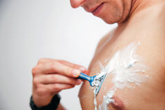 Young man shaving his chest. Torso using a gel and a razor stock photography