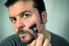 Young man shaving. His face Stock Photography