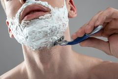 Young man shaving his stubble with disposable razor. Close up portrait of guy with shaving cream on his face removing unwanted facial hair.  on blue-gray royalty free stock photography