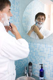 Young man shaving in mirror Stock Photo