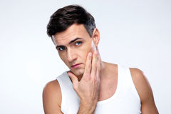 Young man after shaving. Over gray background stock image