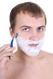 Young man shaving with razor Royalty Free Stock Photography