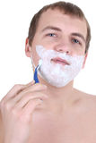Young man shaving with razor Stock Photography