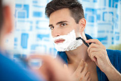 Young man shaving using a razor. Close up of a young man shaving using a razor royalty free stock photos