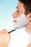 Young man shaving using razor with cream foam. Royalty Free Stock Photo