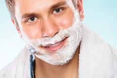 Young man shaving using razor with cream foam. Stock Image