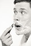 Young man shaving using razor with cream foam. Stock Photos