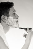 Young man shaving using razor with cream foam. Royalty Free Stock Photography