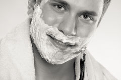 Young man shaving using razor with cream foam. Stock Photography
