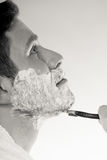 Young man shaving using razor with cream foam. Royalty Free Stock Image