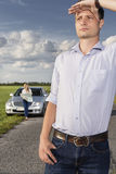 Young man shielding eyes with woman and car in background at countryside Royalty Free Stock Photos