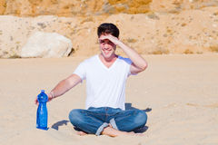 Young man shielding his eyes in desert. Young man shielding his eyes from burning desert sun while reaching for a bottle of water Royalty Free Stock Photography