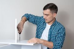 A young man in a shirt in a cage with a screwdriver collects a desktop with a copy of space stock image