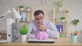 Young man in a shirt and glasses sitting in the office puzzled looks at the piggy Bank. Young man in a shirt and glasses sitting in the office at the table stock video