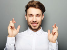 Young man in shirt keeping fingers crossed while standing agains Stock Images