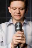 Young man in shirt keeps in hands microphone Royalty Free Stock Photography
