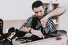 Young Man in Shirt Repairing Snowboard at Home. Man and Hobby. White Room. Engineer with Tool. Young Man at Home. Equipment for Winter. Extreme Hobby. Modern Stock Photo