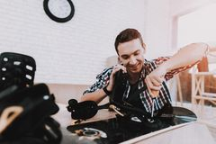 Young Man in Shirt Repairing Snowboard at Home. Man and Hobby. White Room. Engineer with Tool. Young Man at Home. Equipment for Winter. Extreme Hobby. Modern Stock Image