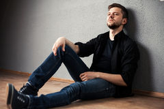 Young man in shirt siting with hands clasped Royalty Free Stock Images