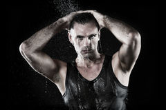 Young man with shirt taking shower Stock Photography