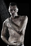 Young man with shirt taking shower Stock Photos