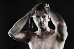Young man with shirt taking shower Royalty Free Stock Images