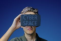Man uses VR. Young man in a shirt uses virtual reality glasses with the inscription `cyberspace` on them in front of a blue background stock photos