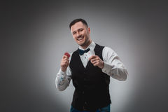 Young man in shirt and waistcoat shows his cards and holds poker chips in his hands, studio shot Stock Photography