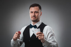 Young man in shirt and waistcoat shows his cards and holds poker chips in his hands, studio shot Royalty Free Stock Images