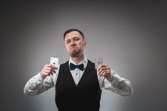 Young man in shirt and waistcoat shows his poker cards, studio shot Stock Photography