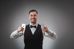 Young man in shirt and waistcoat shows his poker cards, studio shot Royalty Free Stock Photos