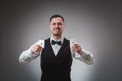 Young man in shirt and waistcoat shows his poker cards, studio shot Stock Photo