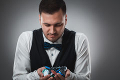 Young man in shirt and waistcoat shows his poker chips, studio shot Stock Image