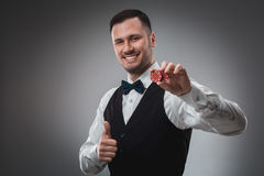Young man in shirt and waistcoat shows his poker chips, studio shot Royalty Free Stock Image
