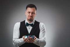 Young man in shirt and waistcoat shows his poker chips, studio shot Royalty Free Stock Photo