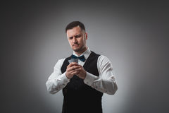 Young man in shirt and waistcoat watch his poker cards, studio shot Royalty Free Stock Photography