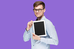 The young man in a shirt working on laptop on lilac backgroundin Stock Images
