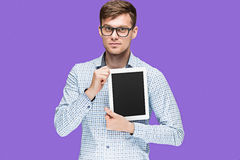 The young man in a shirt working on laptop on lilac backgroundin Stock Image
